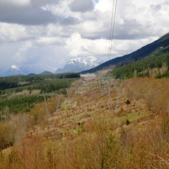 View of the road under the powerlines with mountains in the distance.
